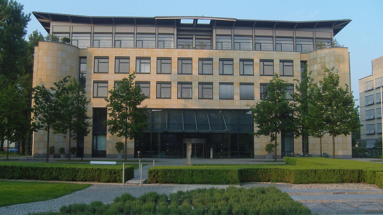4 stöckiges hellbraunes Gebäude mit großer Fensterfront mit 6 grünen Laubbäumen und akurat geschnittenen kleinen Hecken, die die Gehwege davor umrahmen