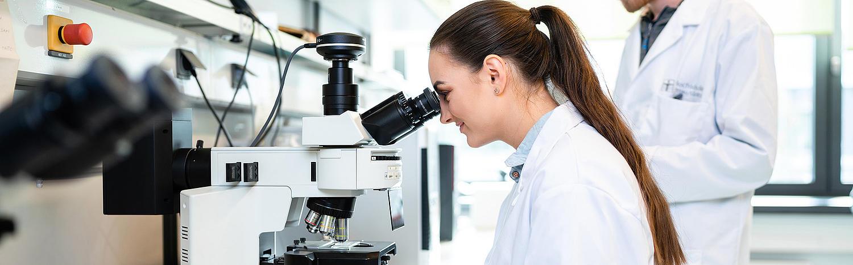 Bachelor Molekulare Biotechnologie: Studierende schaut durch Mikroskop