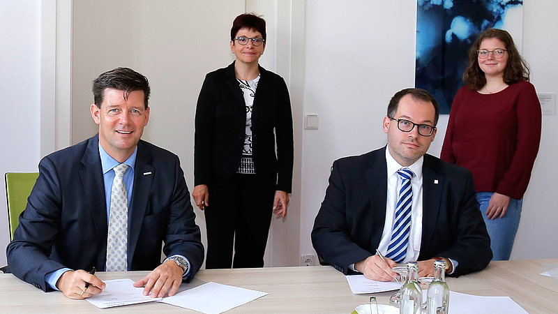 Frank Kebbekus und Prof. Dr. Alexander Kratzsch im Vordergrund bei der Vertragsunterzeichnung. Im Hintergrund Kanzlerin Karin Hollstein und Studentin Nicola Bell.