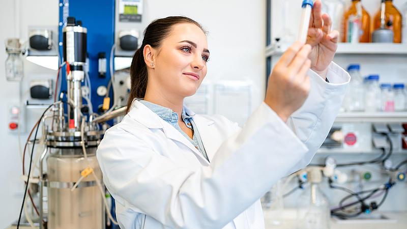 Studentin im weißen Laborkittel begutachtet ein Reagenzglas.