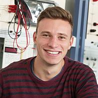 Junger Mann lacht in die Kamera. Im Hintergrund Labor der Elektrotechnik.
