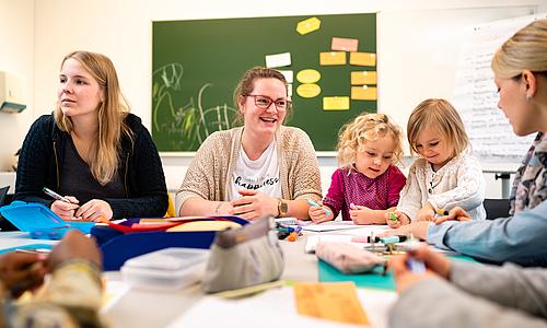 Mehrerer weibliche Studentin, wobei 2 Ihre kleinen Töchter neben sich sitzen haben. Alle befinden sich in einem Seminar.