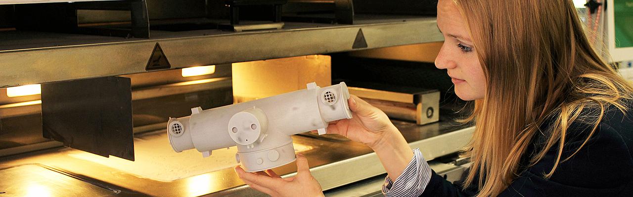 Master Studium Maschinenbau in Zittau: Junge Frau betrachtet Kunststoffteil aus dem 3D Drucker