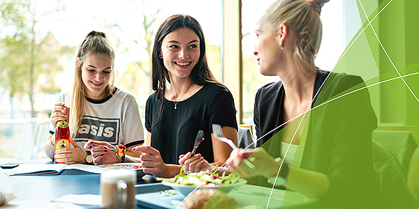 Drei junge Frauen sitzen in der Mensa und essen.