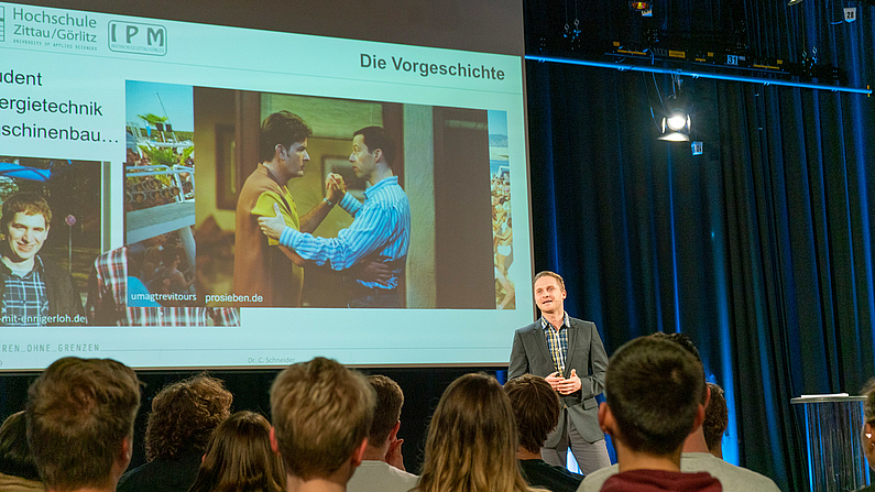 Mann steht vor einer Leinwand, auf der eine Präsentation projeziert wird. Im Vordergrund Publikum von hinten.ordergrund Publikum.