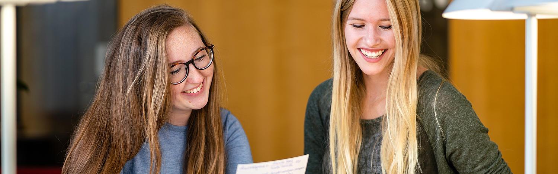 Master of Arts Fachübersetzen Wirtschaft Deutsch/Polnisch - Zwei lachende Studentinnen lesen etwas von einem Zettel ab.