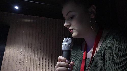 Studentin Agata spricht in einem abgedunkelten Raum in ein Mikrofonal
