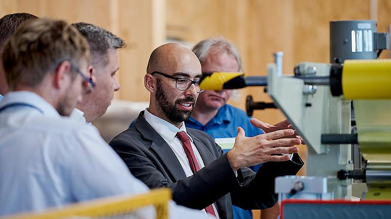 Ein junger Mann mit Brille erklärt anderen Männern etwas vor einer Anlage.