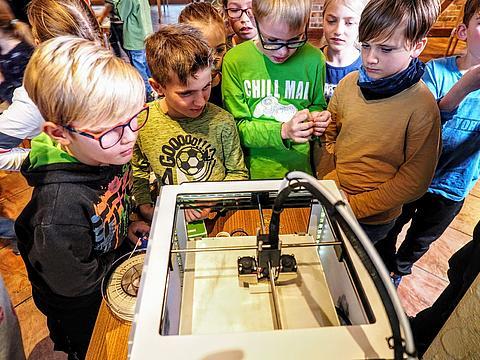 Kunder stehen vor dem 3D-Drucker und schauen ihm beim Druck zu
