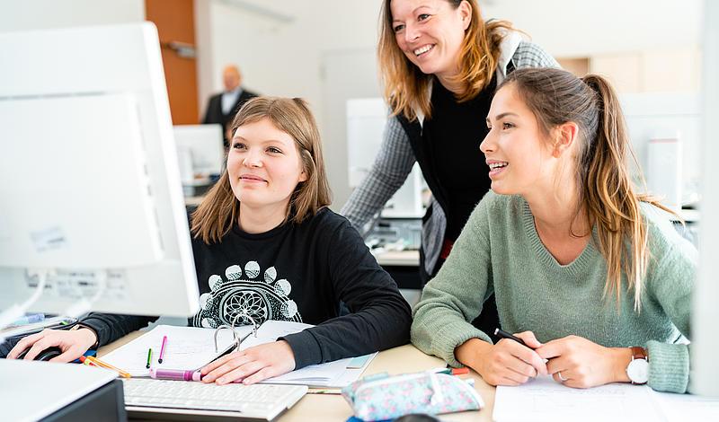 Zwei Studentinnen sitzen vor dem Rechner. Professorin steht dahinter und erleutert Dinge.