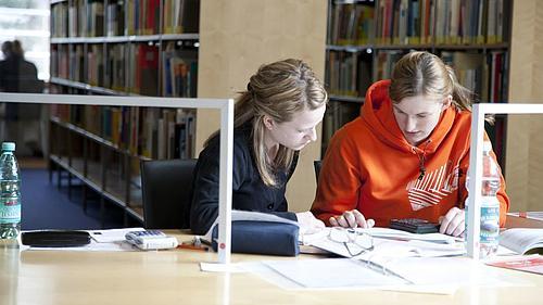 Zwei Studentinnen beim Lernen in der Bibliothek.