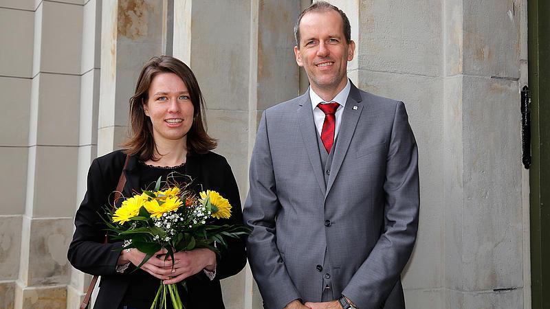 Frau mit Blumenstrauß und Mann im Anzug
