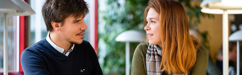 Internationales Tourismusmanagement - Master Studium in Görlitz: Junger Mann mit dunklen Haaren und junge Frau mit roten Haaren, führen ein Gespräch.