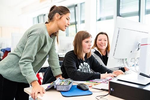 3 Studentinnen sitzen vor einem PC und arbeiten
