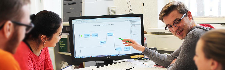 Master-Studium Integrierte Managementsysteme: Gruppe von Studierenden arbeiten zusammen vor einem Bildschirm.