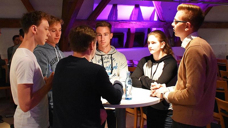 Gruppe von Studierenden stehen an einem runden Tisch und unterhalten sich.