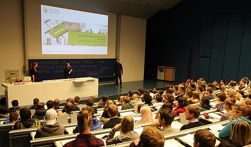 Die Berater für ausländische Studis stellen sich vor in einem Vorlesungssaal voll mit Studenten.