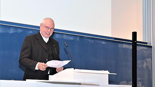 Mann im schwarzen Jacket hält eine Rede