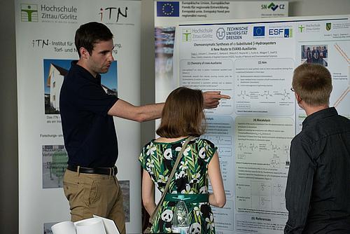 Ein Forschungsmitarbeiter zeigt zwei Besuchern an der Posterwand seine Forschung
