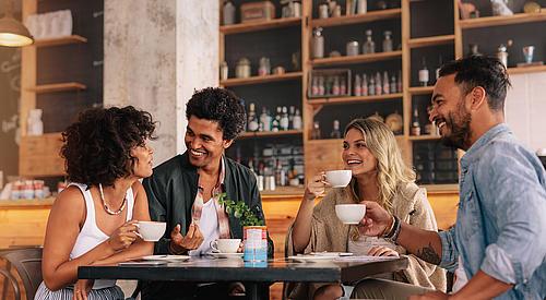 Vier junge Menschen mit unterschiedlicher Nationalität sitzen an einem Tisch und trinken aus Tassen