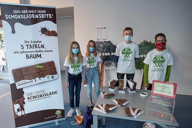 Vier Schüler stehen neben Roll Up mit Werbebotschaft. Vor ihnen befindet sich ein Tisch mit der Schokolade.
