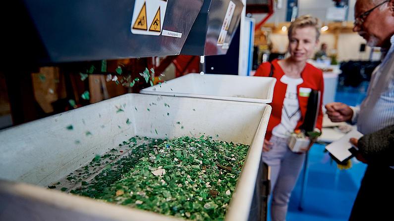 Grünee Kunststoffschnipsel kommen aus einer Anlage.