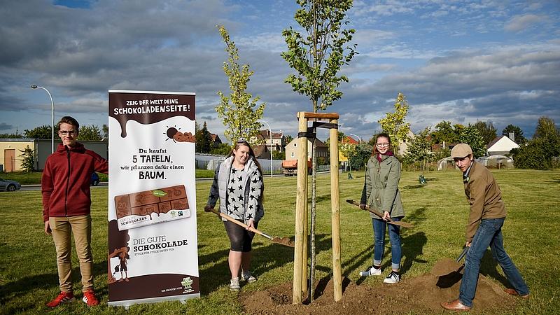 Vier Personen pflanzen einen Baum. Daneben steht ein Roll Up mit der Werbebotschaft.