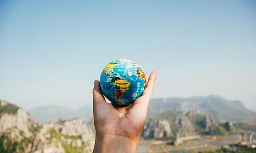 Eine Hand hält einen kleinen Globus vor dem Hintergund einer suptropischen Landschaft.