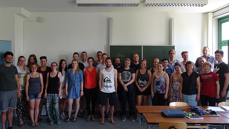 Circa 20 Absolventen und Absolventinnen des TÜV-Zertifaktskurses der Hochschule Magdeburg-Stendal stehen in einem Seminarraum.