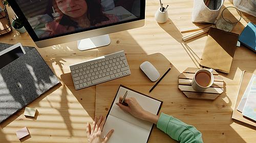 Tisch mit PC, Maus, Tastatur, Kaffeetasse, Stiften und Person die im Notizbuch schreibt. Nebenbei läuft Videokonferenz auf dem PC.