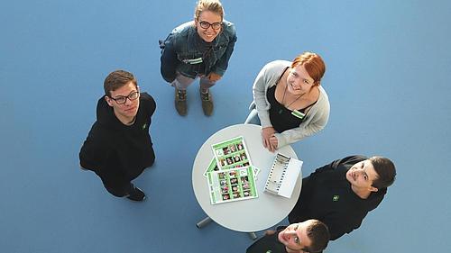 Fünf Ansprechpartner für Studieninteressierte stehen um einen Stehtisch und werden von Oben fotografiert