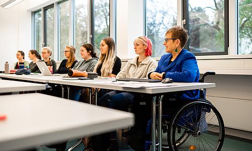 Seminarsituation mit mehreren Studierenden. Am Tischende sitzt die Professorin, die in einem Rollstuhl sitzt.
