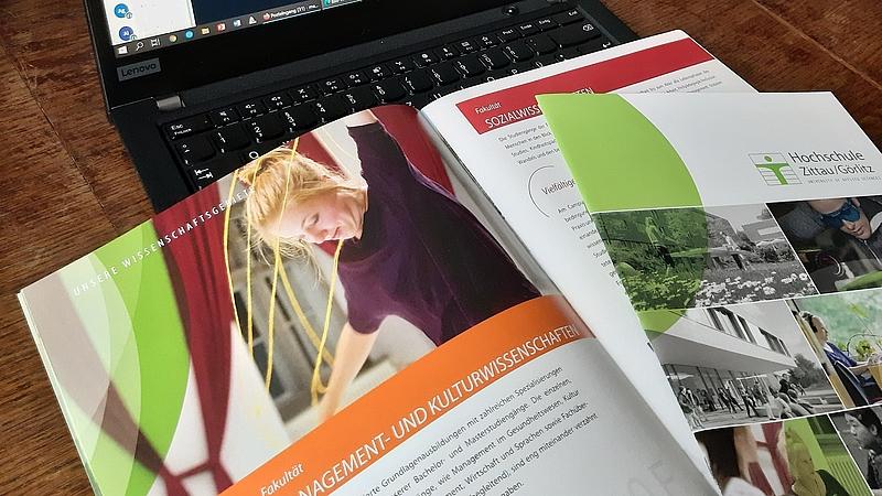 Imagbroschüre der HSZG, bei der die Seite der Fakultät Management- und Kulturwissenschaften geöffnet ist. Broschüre liegt auf der Tastatur eines Laptops.
