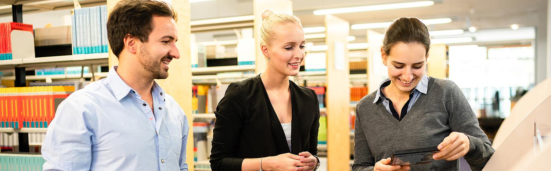 Bachelor Studium Betriebswirtschaft - Drei studierende recherchieren in der Hochschulbibliothek