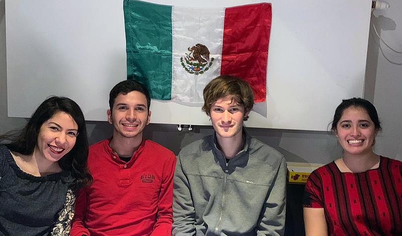 Vier Studierende sitzen vor einer mexikansichen Flagge.