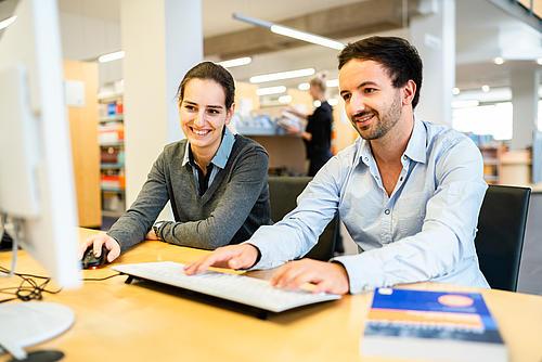 Zwei Studierende (männilich und weiblich) sitzen vor einem Computerbildschirm