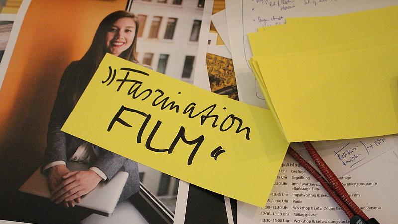 Ein Notizzettel mit der Aufschrift Faszination Film liegt auf Workshopmaterialien auf dem Tisch.