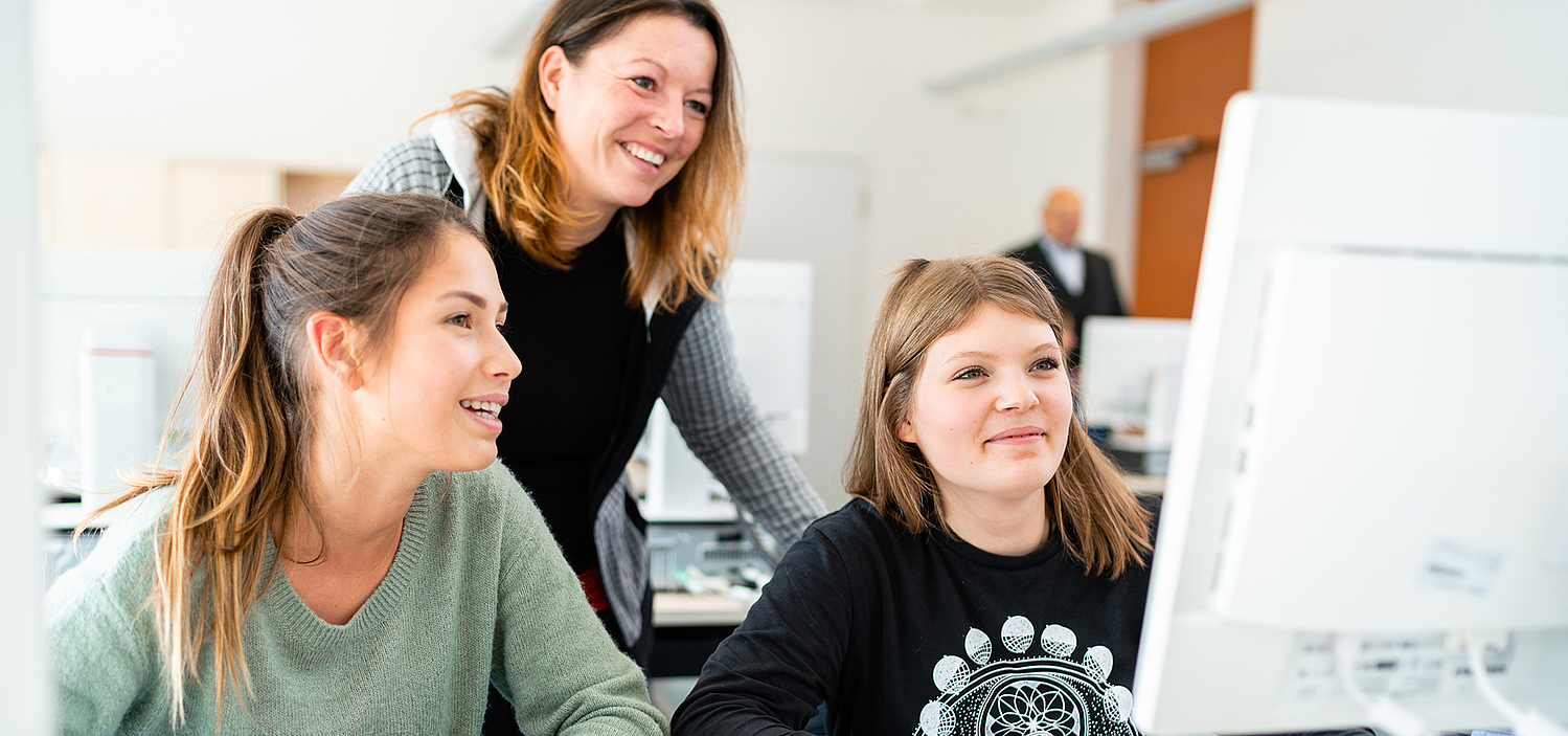 Two female students and their teacher are looking into a computer screen