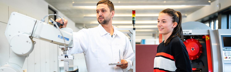 Diplom Studium Wirtschaftsingenieurwesen in Zittau: Lehrkraft und Studentin stehen vor einem Roboterarm.