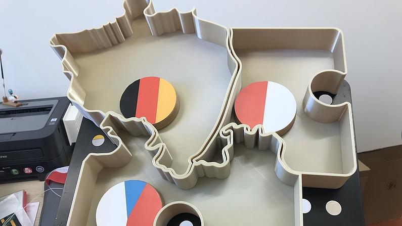 Dargestellt ist ein 3D-Druckmodell der Region Dreiländereck Deutschland, Polen und Tschechien. Die drei Länder werden durch runde Scheiben welche die jeweilige Flaggen symbolisieren dargestellt.