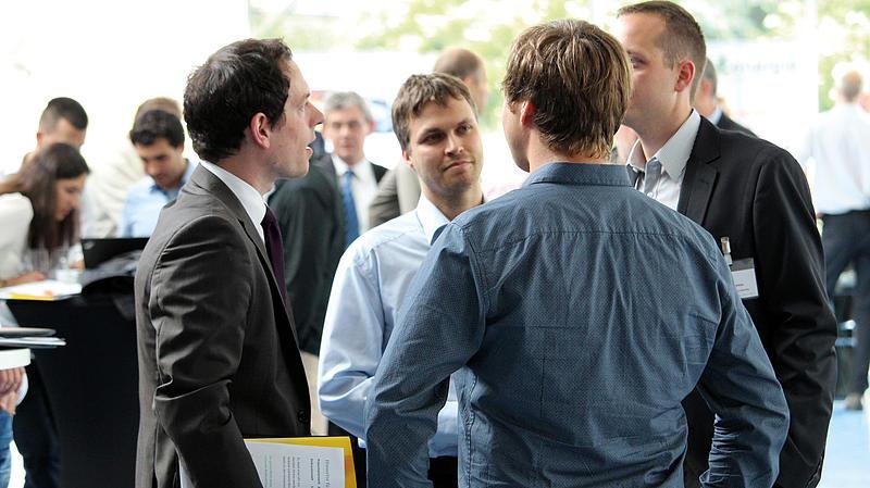 Mehrere Männer im Gespräch auf einer Tagung