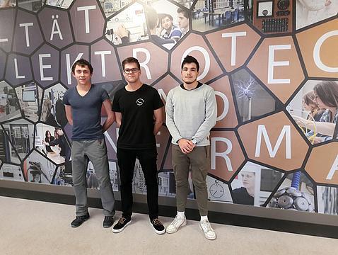 3 junge KIA Studenten vor Wand mit Grafiken im Haus 1 Erdgeschoss