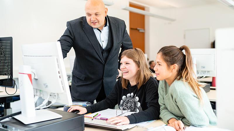 Hochschullehrer erklärt zwei Studentinnen etwas am Monitor