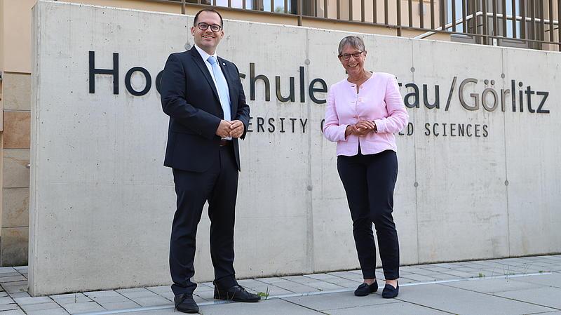 """Der Rektor Professor Alexander Kratzsch und die Staatssekretärin Andrea Franke stehen vor dem Schriftzug """"Hochschule Zittau/Görlitz"""""""