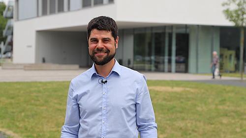Professor Sebastian Scholz vor einem Gebäude der HSZG