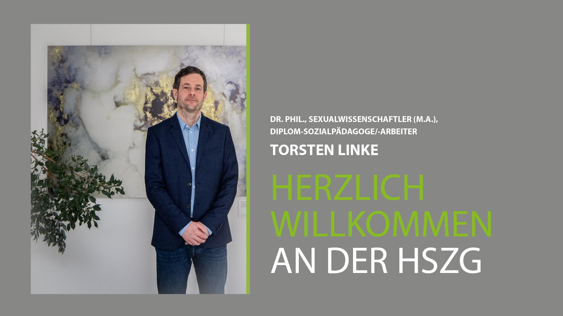 Prof. Linke steht vor einem Gemälde im Haus I der HSZG. Er trägt einen dunkelblauen Anzug und guckt stolz in die Kamera. Er wurde am 1.3.20 an die HSZG berufen.