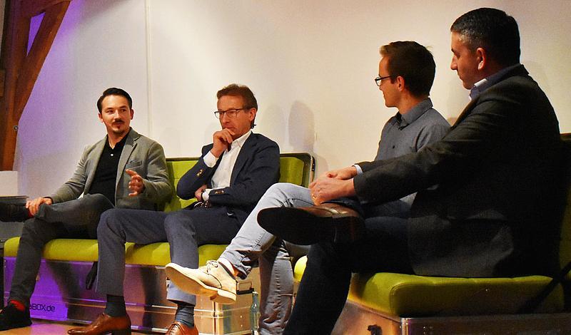 Vier Männer sitzen auf einem Podest auf zwei grünen Sofas