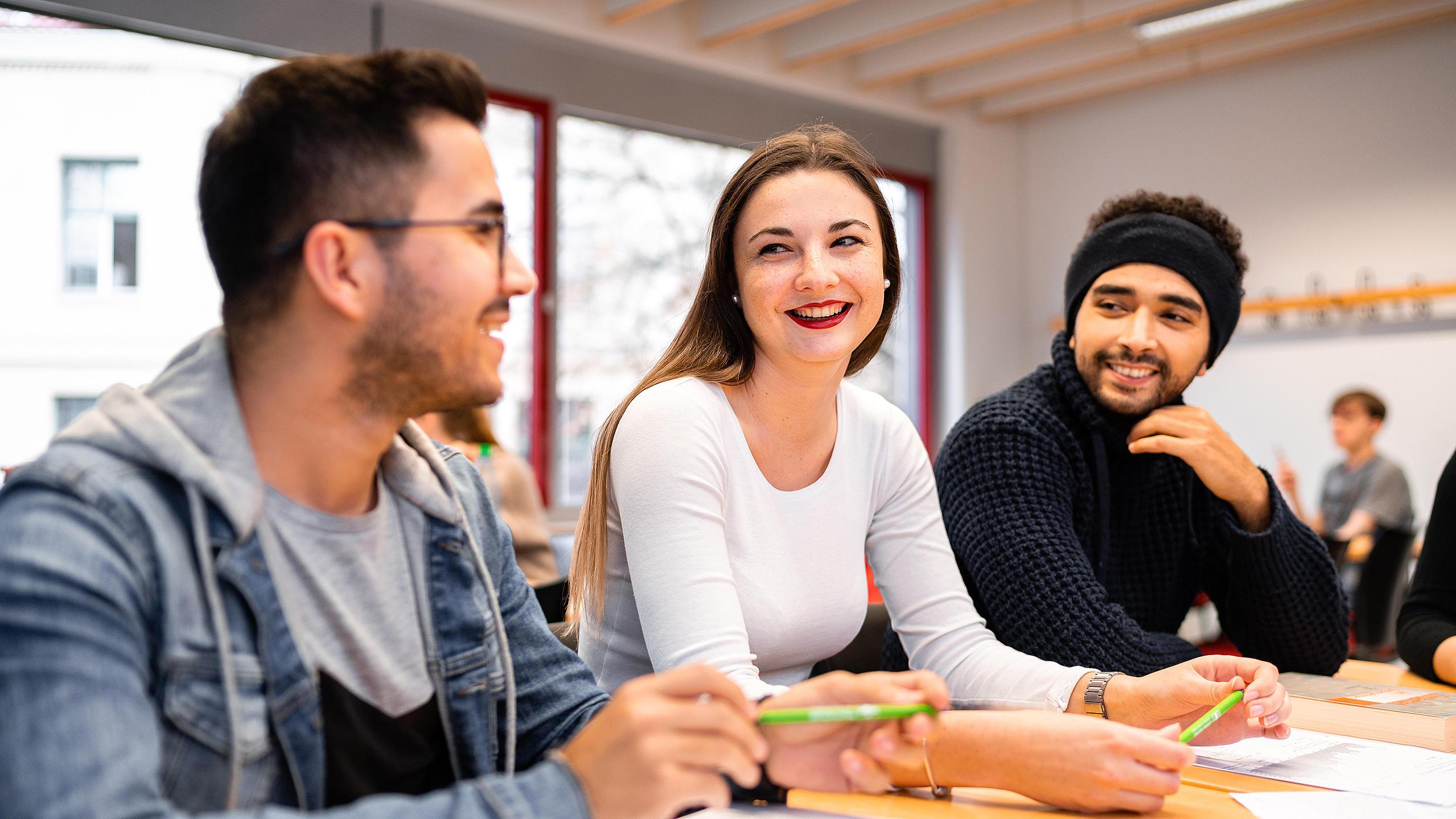 Drei Studierende sitzen am Tisch, unterhalten sich und lachen dabei.